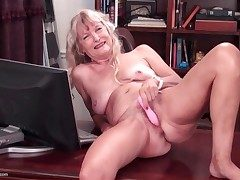 Nude granny on a desk drains her honeypot